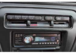 Комбинация кнопок электроприводов с древними ползунковыми регуляторами системы вентиляции и обогрева салона для модели 90-х г. в. выглядит странновато.