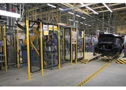 Один из трех роботов на заводе наносит клей на лобовое стекло. Топливный бак перед установкой проверяют на герметичность прямо на конвейре.