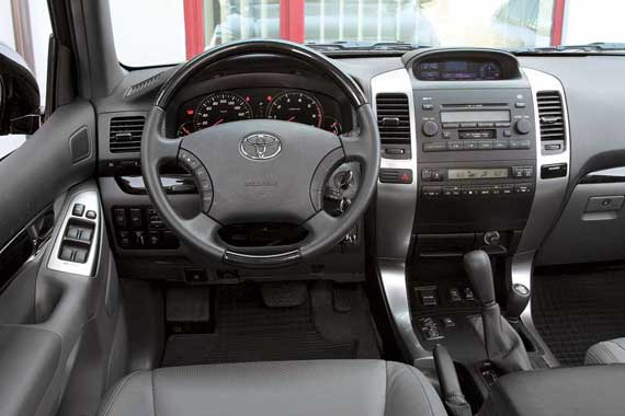 За счет отделки алюминием и черным деревом интерьер Toyota выглядит солиднее. Недостатком салона Prado можно назвать малое количество ниш для подручной мелочевки. Забавно сегодня видеть в таком авто не только CD, но и кассетную деку.