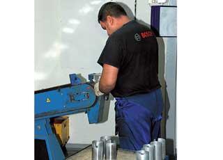 Очаги коррозии на корпусе стартера удаляют на специальном станке с помощью наждачной бумаги.