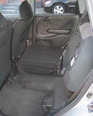 Внутри Jazz очень просторный – зарослым водителем сзади усядется такой же рослый пассажир, и коленями вспинки сидений он упираться не будет. Фирменная система трансформации задних кресел: их подушки можно поднять, закрепив на спинках, или же полностью положить спинки напол, получив ровную грузовую площадку.