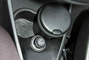 Мест для мелких вещей в Lancia Ypsilon совсем немного. Подстаканники спереди годятся исключительно длястаканчиков, абутылки будут упираться впологий подиум ручки переключения передач.