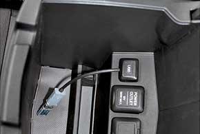 В недрах просторного бокса между передними сиденьями – 12-вольтная розетка, разъем под USB и «тюльпан» для подключения видеоустройств.