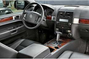 Салон Touareg напоминает легковое авто с тщательно выверенной эргономикой. Полный привод и пневмоподвеска управляются компактными вращающимися регуляторами. На машинах первых годов выпуска оснащение огорчало отказами.