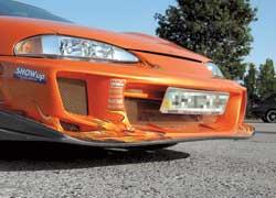 Mitsubishi Eclipse. Экстерьер усовершенствован припомощи пакета обвеса Bomex Aero, включающего пару бамперов и пару накладок на пороги. Своим умопомрачительным цветом машина обязана японской перламутровой краске Maziora Orange.