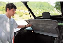 Полка не «привязана», поэтому ее надо поднимать руками при каждом открывании багажника.