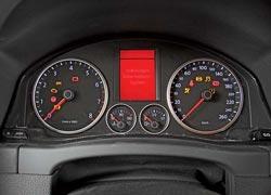 Щиток стандартный, но во «внедорожной» комплектации VW Tiguan на нем появился компас (1), а также значок активированной системы помощи при спуске с горы Hill Descent Control (2).
